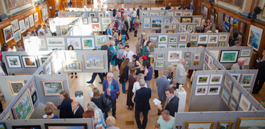 Many people are observing works of art at the Chelsea Art Society Exhibition
